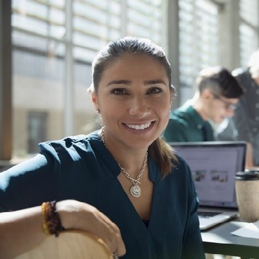 smiling girl sitting at a desk with laptop