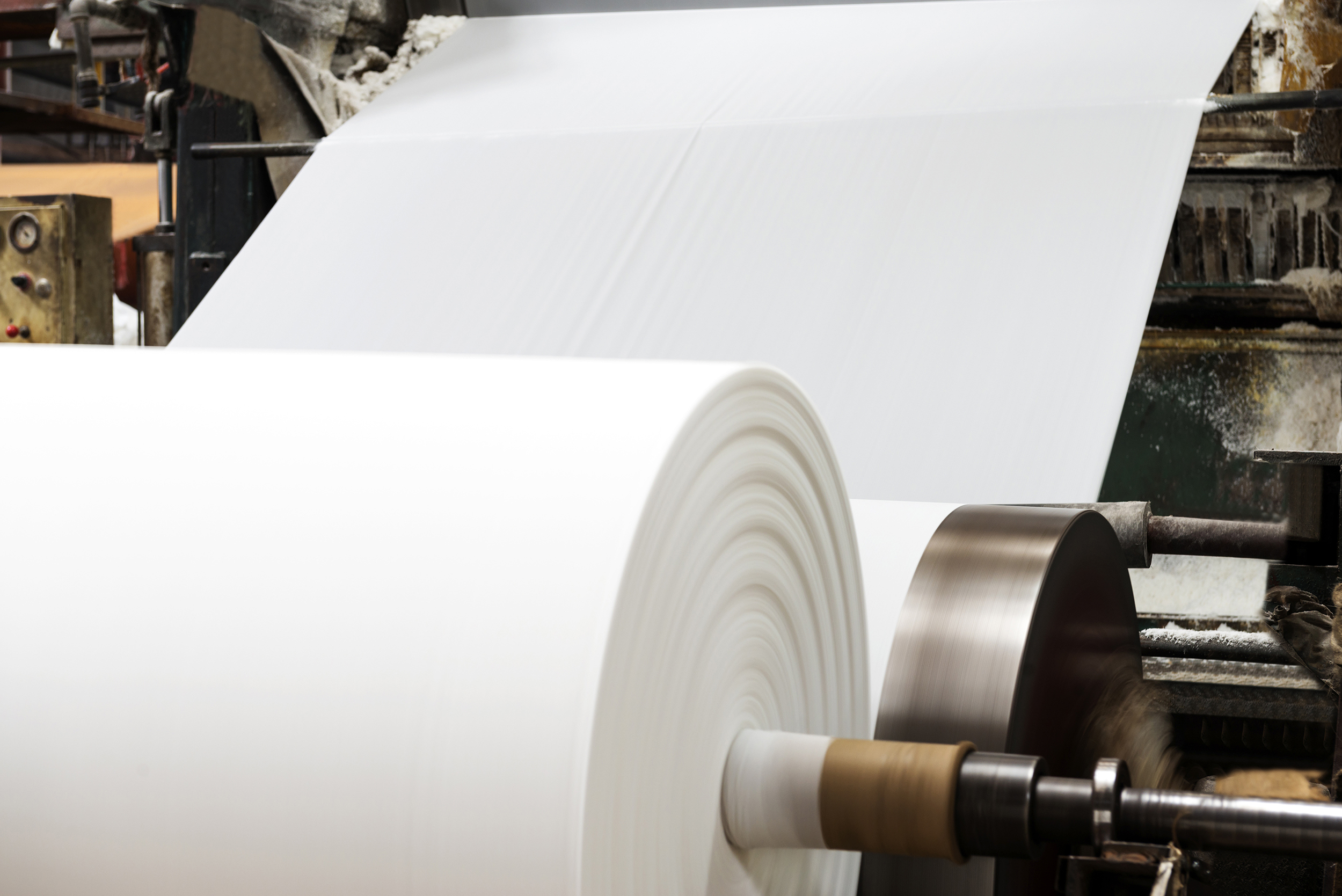 Roll of industrial-sized paper going into a machine