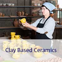 Woman working on yellow clay pots and cups