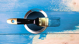 Paint Can and Brush on Blue Wood