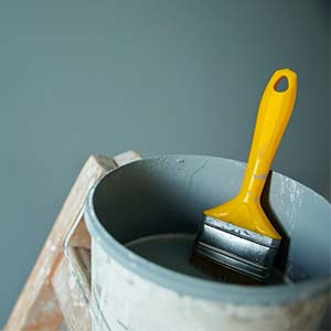 Gray can of paint with yellow paint brush