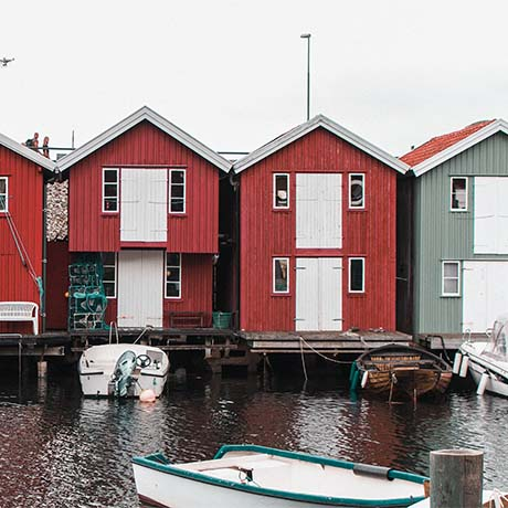 Red houses along bay with boats in the water
