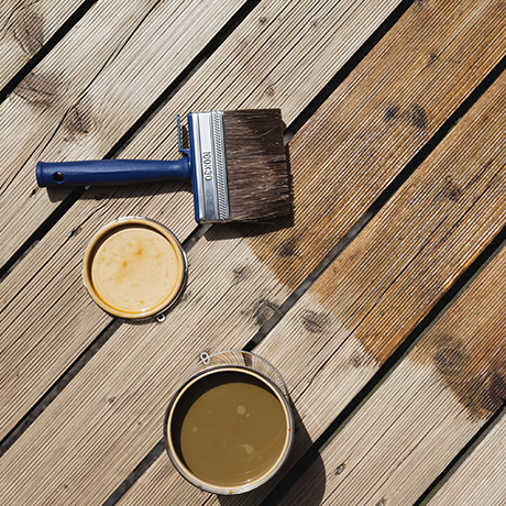 Paint cans and brush on wooden deck