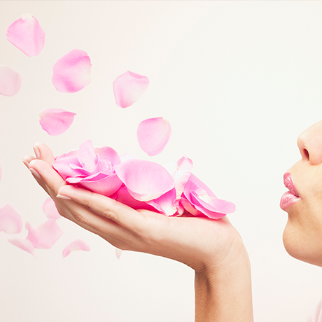 Woman blowing pink petals in the air