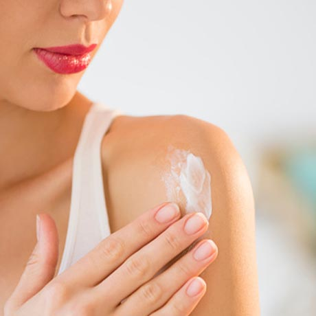 Woman rubbing lotion onto shoulder
